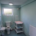 Toilet with handrail and baby changing facility